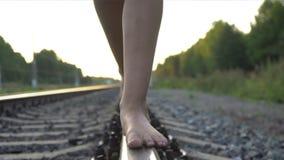 Jeune fille marchant nu-pieds le long du rail de chemin de fer banque de vidéos