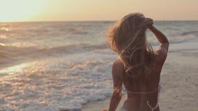 Jeune fille marchant près du bord de mer sur le coucher du soleil clips vidéos