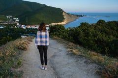 Jeune fille marchant sur une route de montagne avec la vue de ville enveloppée dans une couverture Soirée fraîche d'été dos Image libre de droits