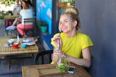 Jeune fille merveilleuse souriant largement, verre de prises à disposition, boisson Image stock