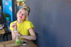 Jeune fille merveilleuse souriant, verre de prises à disposition, buvant le lemo Image libre de droits