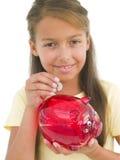 Jeune fille mettant la pièce de monnaie dans la tirelire images stock
