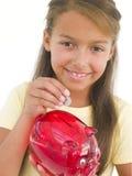 Jeune fille mettant la pièce de monnaie dans la tirelire photo stock