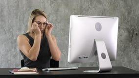 Jeune fille mettant sur des verres et débuts travaillant à l'ordinateur se reposant à la table image stock