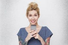Jeune fille mignonne avec des tatouages au-dessus de ses bras portant le smartphone accrochant et le sourire de T-shirt bleu occa Photos stock