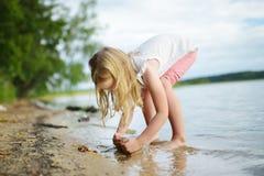 Jeune fille mignonne ayant l'amusement sur une plage arénacée de lac le jour chaud et ensoleillé d'été Enfant jouant par la riviè image libre de droits