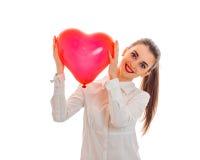 Jeune fille mignonne dans la chemise souriant et tenant un grand ballon en forme de coeur Images libres de droits