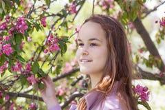 Jeune fille mignonne dans un champ de pommiers Photo stock