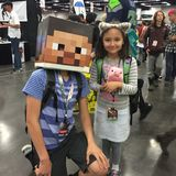 Jeune fille mignonne de costume avec le caractère de Minecraft Steve photographie stock