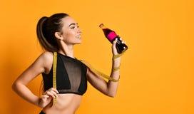 Jeune fille mignonne de forme physique dans des regards noirs de costume dans la caméra et maintenir la bande et la bouteille de  photo stock