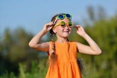 Jeune fille mignonne en verres de soleil ayant l'amusement dehors Photographie stock libre de droits