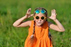 Jeune fille mignonne en verres de soleil hamming ayant l'amusement dehors Image libre de droits