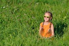 Jeune fille mignonne en verres de soleil se reposant dans l'herbe dehors Image libre de droits