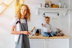 Jeune fille mignonne et sa soeur d'enfant en bas âge préparant le petit déjeuner pour des parents photo libre de droits