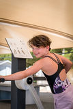 Jeune fille mignonne exerçant le corps supérieur sur la machine de formation de gymnase dehors Images stock