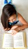 Jeune fille mignonne lisant un livre sur le lit Images stock