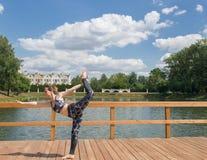 Jeune fille mince dans l'usage gris de sport faisant le yoga sur le pont Jeune fille flexible avec les cheveux rouges Sur l'air photo stock