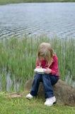 Jeune fille moderne jouant le jeu d'ordinateur en nature Images libres de droits