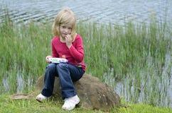 Jeune fille moderne jouant le jeu d'ordinateur en nature Image stock