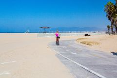 Jeune fille montant un vélo par la plage de muscle Photos stock