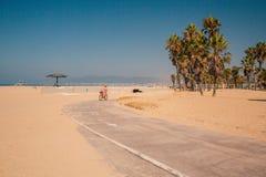 Jeune fille montant un vélo par la plage de muscle Photo libre de droits