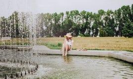 Jeune fille mouillant sa fontaine de piscine de pieds image stock