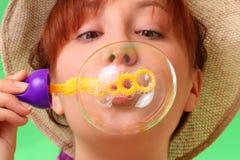 Jeune fille négligente dans les bulles de savon de soufflement de chapeau Photographie stock libre de droits