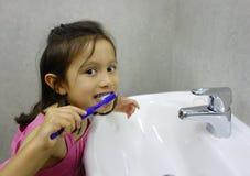 Jeune fille nettoyant ses dents. Photographie stock