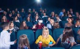 Jeune fille observant 3D-eyeglasses dans le hall de cinéma Photos stock
