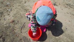 Jeune fille observant les poissons dans le seau rouge banque de vidéos