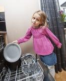 Jeune fille par le lave-vaisselle photographie stock