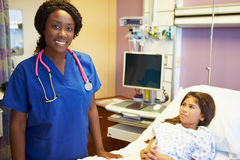 Jeune fille parlant à l'infirmière féminine In Hospital Room Photos stock