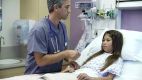 Jeune fille parlant à l'infirmière masculine In Hospital Room banque de vidéos