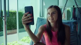 Jeune fille parlant sur Skype au téléphone tout en se trouvant sur un lit accrochant pendant l'après-midi, mouvement lent Plan ra clips vidéos