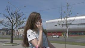 Jeune fille parlant sur un smartphone descendant la rue clips vidéos