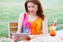 Jeune fille passant en revue le PC à la mode de comprimé Images stock