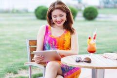 Jeune fille passant en revue le PC à la mode de comprimé image libre de droits