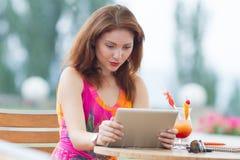 Jeune fille passant en revue le PC à la mode de comprimé Photographie stock libre de droits