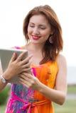 Jeune fille passant en revue le PC à la mode de comprimé Images libres de droits