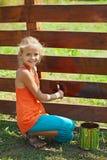 Jeune fille peignant une barrière en bois Image stock