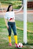 Jeune fille posant avec du ballon de football au but du football photographie stock
