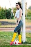 Jeune fille posant avec du ballon de football au but du football image stock