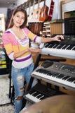 Jeune fille positive choisissant le synthétiseur Photos libres de droits