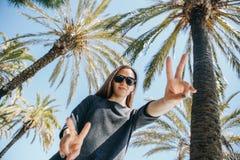 Jeune fille positive, ou un touriste heureux sur un fond des palmiers et du ciel bleu dans un pays chaud Photographie stock