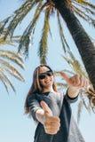 Jeune fille positive, ou un touriste heureux sur un fond des palmiers et du ciel bleu dans un pays chaud Photos libres de droits