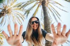Jeune fille positive, ou un touriste heureux sur un fond des palmiers et du ciel bleu dans un pays chaud Photo libre de droits