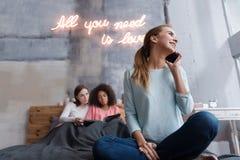 Jeune fille positive parlant au téléphone dans la chambre à coucher Photo stock