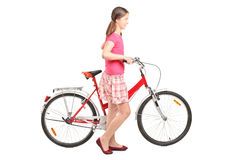 Jeune fille poussant un vélo Photos stock