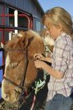 Jeune fille préparant son poney Photographie stock libre de droits