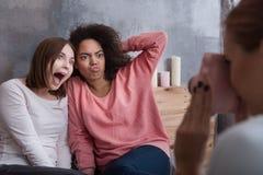 Jeune fille prenant la photo de ses amis à la maison Image libre de droits